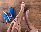 stock photo of knee-cap  - Unrecognizable injured runner sitting on a wooden floor background - JPG