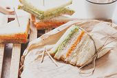 foto of tomato sandwich  - fresh sandwich filled with tomato and lettuce cream on paper - JPG