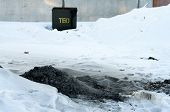 stock photo of ashes  - Ashes thrown into the snow next to a container for waste - JPG
