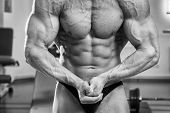 foto of abdominal muscle man  - A man pumping abdominal muscles in the gym - JPG