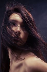 image of gothic hair  - bared woman with fluffy hair looking back toned image - JPG