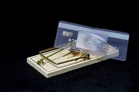 stock photo of mouse trap  - A credit card sitting on a trigger of a mouse trap - JPG