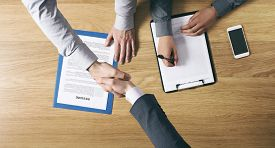 stock photo of hands up  - Employer hiring and giving an handshake to the candidate after the job interview hands close up top view - JPG