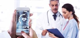 picture of x-files  - Hand holding smartphone against nurse and doctor looking a file - JPG