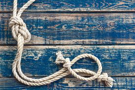 stock photo of marines  - Vintage wooden background with knotted marine rope - JPG