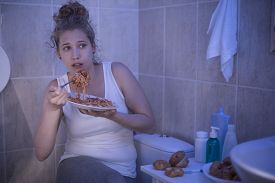 stock photo of bulimic  - Picture of female ashamed of her illness eating in bathroom - JPG