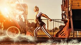 picture of train-wheel  - Blond woman in steampunk clothes is pulling a retro train - JPG