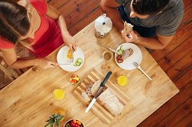 pic of breakfast  - Top view of couple enjoying a healthy morning breakfast in kitchen at home - JPG