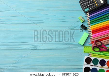 poster of school and office supplies. school background. colored pencils, pen, pains, paper for  school and student education on blue wood background. top view with copy space