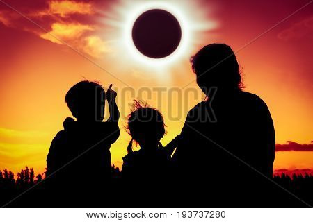 poster of Silhouette back view of family sitting and relaxing together. Boy point to solar eclipse on gold sky background. Happy family spending time together. Outdoor.