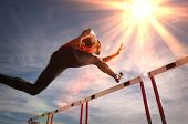 Runner jumping over running hurdle, low angle view poster