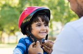 Father helping cheerful son wearing helmet for cycle. Excited little boy getting ready by wearing bi poster
