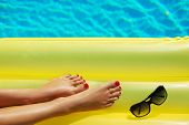 Portrait Of Beautiful Tanned Woman Relaxing In Swimming Pool. Sunglasses And Inflatable Matress. Leg poster
