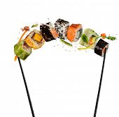 Sushi pieces placed between chopsticks, separated on white background. Popular sushi food. Very high poster