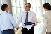 Foto de handshaking de parceiros de negócio bem sucedido depois da impressionante grande com jovem colega nea