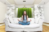 Young Woman sitting on Sofa in der Lotus-Position in einer Umgebung mit Zen Meditation