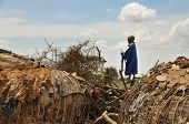 OLDUVAI GORGE, TANZANIA, DECEMBER 23, 2011, YOUNG MAASAI BOY STANDS ON FENCE AT EDGE OF VILLAGE AND