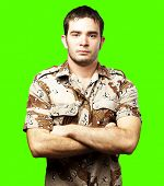 portrait of a serious young soldier standing against a removable chroma key background