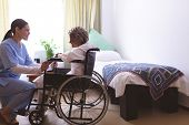 Side view of mixed race nurse talking with senior mixed race female patient at nursing home. Senior  poster