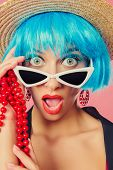 Close-up portrait of a funny girl with bright blue hair wearing pin-up sunglasses over pink backgrou poster