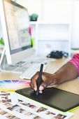 Close-up of young African-American graphic designer working on graphic tablet at desk in office poster