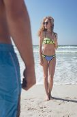 Front view of beautiful young Caucasian woman standing at beach on a sunny day. Caucasian male in th poster