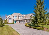 Beautiful exterior of newly built luxury home. Yard with green grass and walkway lead to ornately de poster