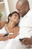 A happy African American man and woman couple in their thirties sitting at home together smiling and