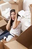 A beautiful single young woman screaming with stress while unpacking boxes and moving into a new hom