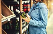 Customer Buying White Wine Or Sparkling Drink. Alcohol Aisle In Store Or Supermarket. Woman Holding  poster