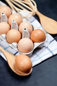 Eggs and kitchen utensil closeup on backboard background. Eggs, wooden spoon, whisker, towel and oth poster