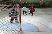 picture of hockey arena  - Young Boys Playing Hockey in front of the Goalie Net - JPG