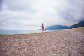 The Girl Runs Along The Beach. Woman Trains In Nature. Brunette Runs On The Background Of The Sea An poster