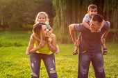 Happy Family -happy Family Piggyback Their Children And Have Fun Together In Park poster