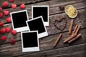 Blank instant photo frames with small heart shapes and cinnamon on old wooden background.
