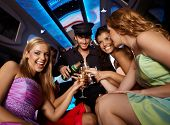 Happy girls having fun in limo, drinking champagne.?