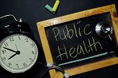 The Words Public Health Handwriting On Chalkboard On Top View. Alarm Clock, Stethoscope On Black Bac poster