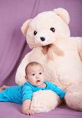 lovely baby boy and a big teddy bear.