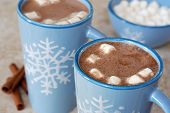 Snowflake mugs filled with hot chocolate and marshmallows on tile counter with cinnamon sticks along