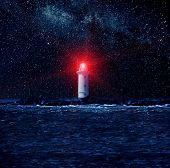 Lighthouse glowing red in a dark starry night