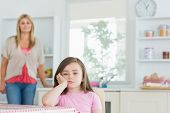 Child sitting at kitchen table looking angry with mother watching on