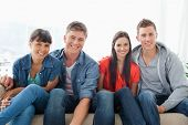 Ein Lächeln Gruppe lehnen nach vorne leicht wie sie in die Kamera schauen, beim Sitzen auf der couch