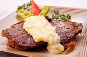 Baked beef steak with mashed potato, on the decorative plate, served on the table