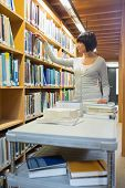Librarian standing and looking through book shelf