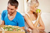 bright picture of couple eating different food (focus on woman)