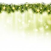 Golden stars in a border of fir twigs on a soft golden green background with blurry lights, light effects and snowfall. Festive and wintry, great background for any Christmas or winter theme.