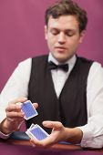 Dealer sitting at table in a casino while shuffling deck of cards