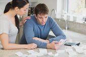 Couple calculating bills in kitchen looking worried
