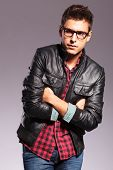 young casual man with glasses and leather jacket with hands folded looking away from the camera