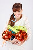 Happy girl in white dress shows green, red and blue boxes with gifts.
